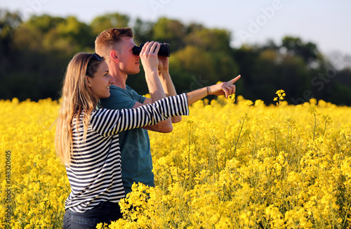 Fotobehang Meloen Junges Paar mit Fernglas auf Entdeckungstour in der Natur