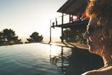 junge Frau schaut am Swimmingpool den Sonnenuntergang an