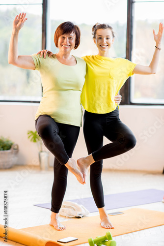 Fototapeta Young and older women in sports wear doing yoga together indoors at home or a gym