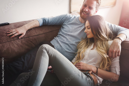 Happy couple  lying on sofa together and relaxing at home