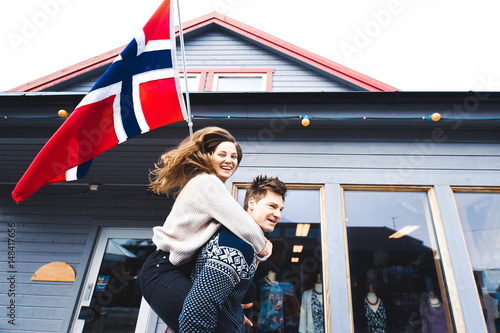 closeup couple girl and man in love Scandinavian style, sweater with deer, kissing and holding hands close a beautiful young blond hair Norwegian flag on a background of happiness