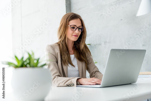 Foto Murales Beautiful Businesswoman typing on laptop