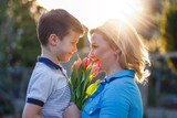 Fototapeta Little boy surprising mom with tulips at Mother's Day
