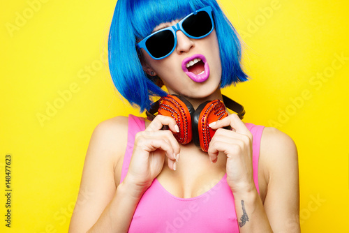 d573e0529 Beautiful young sexy girl dj in blue wig blue sunglasses and pink bathing  suit having fun