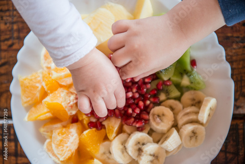 Children taking fruit from the plate