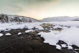 Water stream with rocks in a winter landscape in twilight.