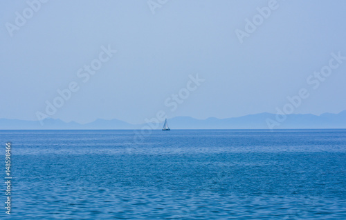 Faraway sailing boat on the blue sea Poster