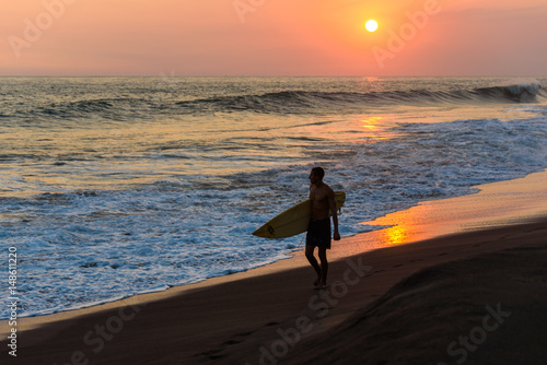 Papiers peints Cappuccino Silhouette of surfer walking on beach at sunset