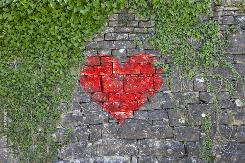 Fotobehang Graffiti Old stone wall with ivy as background and with painted big red heart symbol. Conceptual love background.