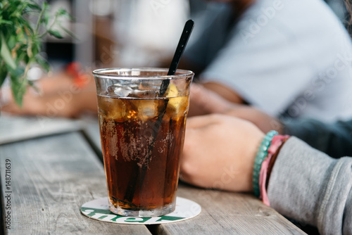 Refreshing glass of cola on wooden table in a bar Poster