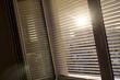 Jalousien als Sonnenschutz am Fenster - 148744097