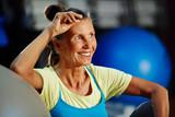 Happy woman in sportswear spending leisure in gym