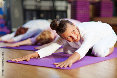 Active and fit woman exercising on mat
