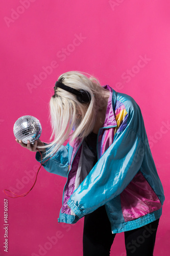 Young woman posing with a disco ball - 148760057