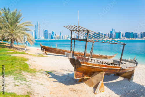 Fotobehang Abu Dhabi Wooden boat at the Heritage Village, in front of the Abu Dhabi skyline, United Arab Emirates