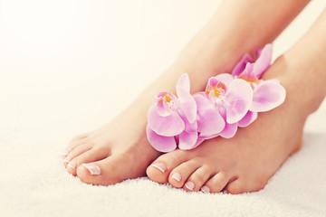 Soft female feet with french pedicure and flowers close up © Kalim