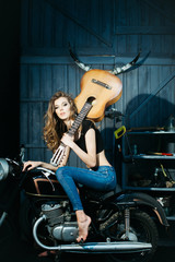 Pretty girl model with guitar sitting on motorcycle