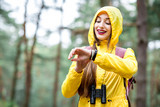 Young woman in yellow raincoat tracking steps with electonic bracelet walking in the green pine forest