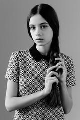 modest girl posing on gray background in Studio