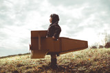 front view vintage pilot boy flight by imagination on cardboard plane outdoor - 148903675