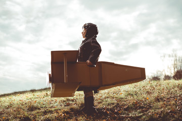 front view vintage pilot boy flight by imagination on cardboard plane outdoor