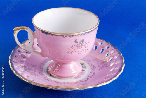 Poster Antique Pink Cup and Saucer on Blue Textured Background