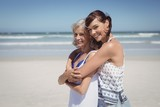 Fototapeta Portrait of happy woman embracing her mother at beach