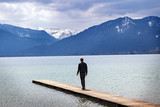 Young man alone on a jetty in the tegernsee lake looks to the mountains, itourist resort of the Bavarian Alps