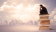 Man sitting on pile of books above city