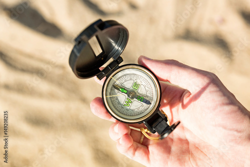 Plakat Male hand with compass on sand background
