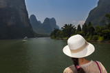 Woman with a hat looking at the landscape in a river cruise in the Li River between Guilin and Yangshuo, in China; Concept for travel in China