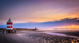 Beautiful sunrise at the seaside in Italy, at Lignano Sabbiadoro, with pier and lighthouse in the foreground.