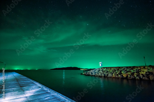 Beautiful calmness starry night sky with cloudy and colorful light at seashore pier