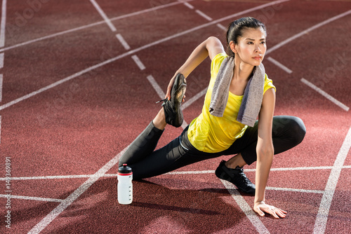 Juliste Woman sprinter doing warm up exercise before sprint