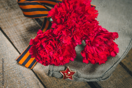 Poster Carnation flowers, George Ribbon and military garrison cap with a red star