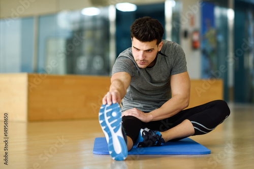 Young man stretching their legs in gym.