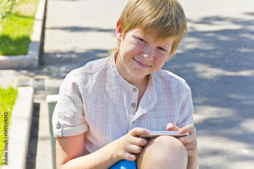 Poster Blond boy with mobile phone sitting on a bench