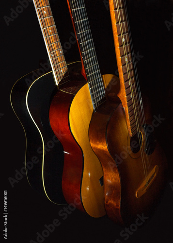 Poster Three acoustic guitars on black background