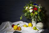 vintage style food still life with various fruit and a bouquet of flowers