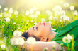 Beautiful young woman lying on the field in green grass and dandelions - 149645049