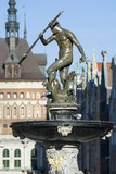 Neptune Fountain - symbol of Gdansk, located at Long Market, blurred Prison Tower and Golden Gate in the background, Poland