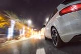 Auto fährt auf beleuchteter Straße