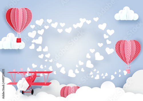 Fototapeta airplane flying over clouds and smoke hearts shape with Cute hot air balloons background. Paper art style