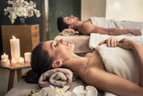 Fototapety Man and woman lying down on massage beds at Asian wellness center