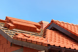 roof under construction with stacks of red ceramic roof tiles ready to fasten - 149773613