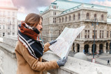 A stylish woman in a coat with a scarf is guided by a map in the center of a European city, the concept of travel