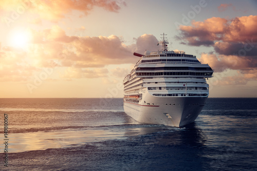 Luxury cruise ship leaving port at sunset Poster
