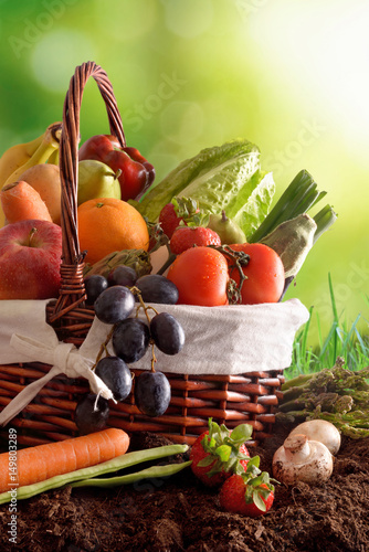 Fruits and vegetables on soil and green background vertical