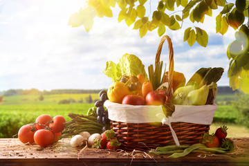 Fruits and vegetables on table and crop landscape background