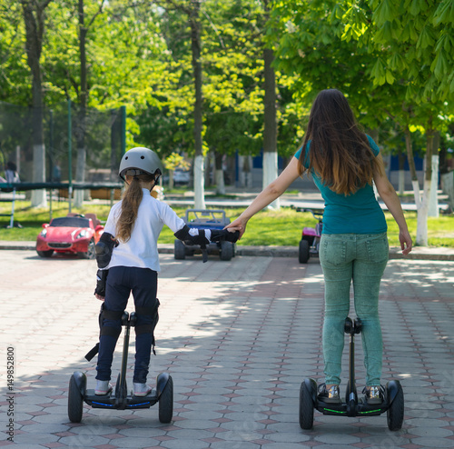 Foto op Canvas Scooter Young mother and daughter riding electric mini hoverboard in park. Family concept. They are holding hands.